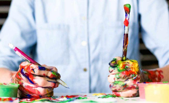 Mann beim Malen mit verschmierten Händen - keine Hinweis auf ein Talentn